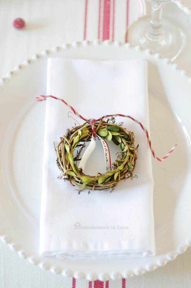 holiday plate serving top off with mini boxwood wreath place cards.
