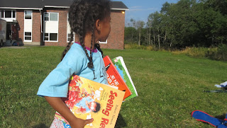child borrows book from storytent on Roxbury