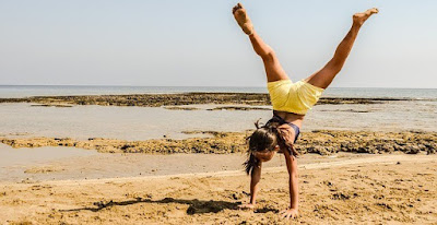 Girl Doing a Hand-Stand on the Beach
