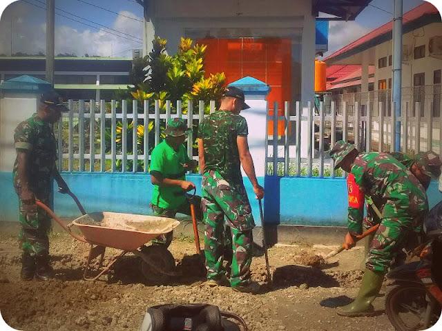 Anggota TNI Bersihkan Lubang Parit Serapan Air di RSUD Biak