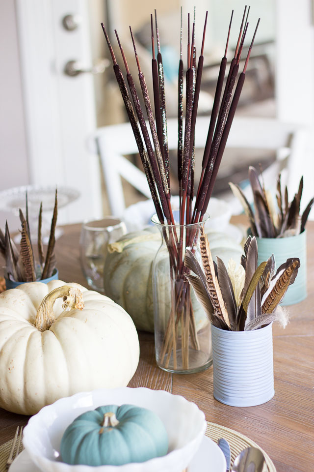A modern Thanksgiving table with gold dipped feather arrangements and pumpkins painted in moody blues and greens    http://designimprovised.com