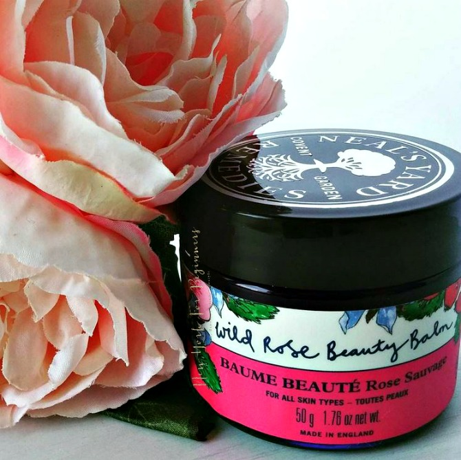 Neal's Yard Wild Rose Beauty Balm with flowers on background