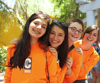 Four teenage girls in orange shirts smiling for the camera at CTeen Summer Camp