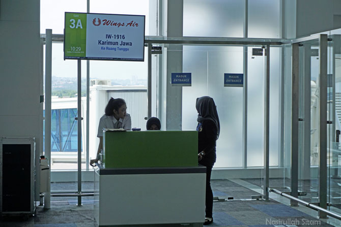 Petugas pada pintu tiga yang mengecek tiket pesawat
