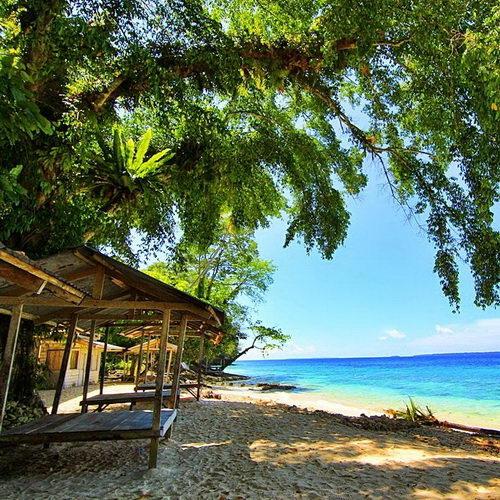 Tinuku Travel Bosnik Beach on Biak island presents unique color gradation coastal seawater, beautiful sand and shady trees