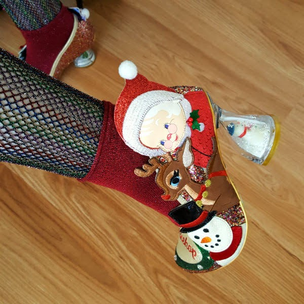 close up of christmas shoe on foot with mrs claus, snowman and reindeer applique characters and perspex heel with snowman