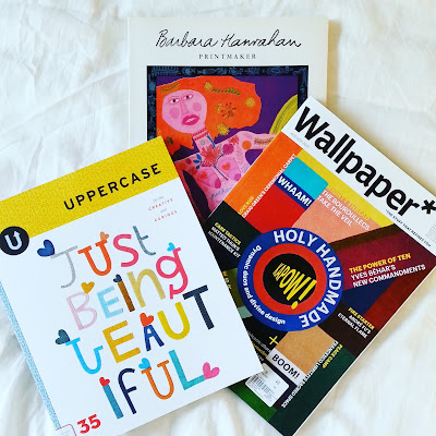 Two magazines (Uppercase and Wallpaper) and a book (Barbara Hanrahan: printmaker) arranged on a bed with white bedding.