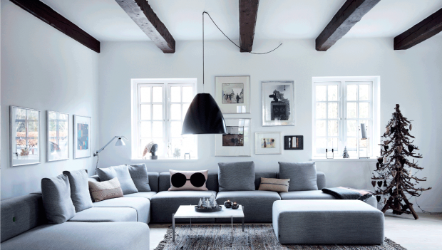 salón decorado para navidad con gran sofá y árbol de navidad en tonos marrones, blancos, negros, grisies y ocres