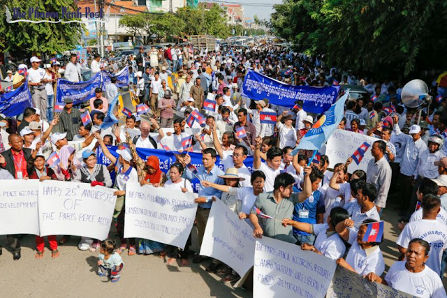 People wave flags and hold placards on the road in front of the CNRP headquarters yesterday in Phnom Penh during an event to mark the anniversary of the signing of the Paris Peace Agreement. Heng Chivoan
