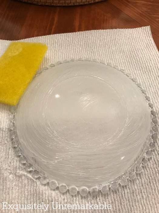 Cleaning a glass dish on a paper towel with a yellow scrubber