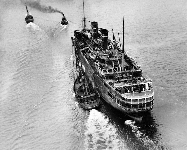 The wreck is towed away to be scrapped, six months after the fire. March 14, 1935.
