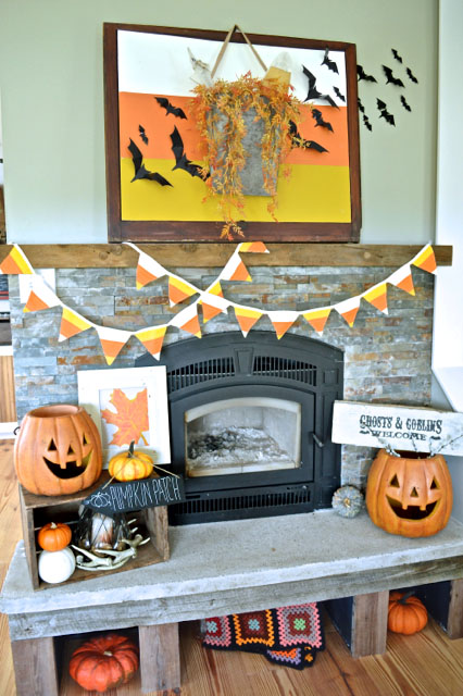 white orange and yellow candy corn decor with banner and pumpkins and wall art.