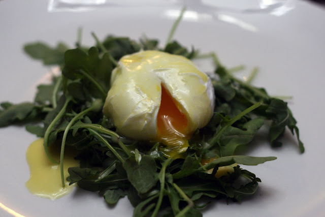 Soft poached eggs with homemade hollandaise sauce on a bed of arugula.