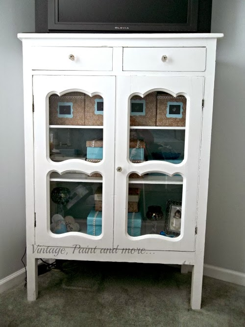 DIY Decorative Box Storage - image of closed cabinet with view of decorative boxes through glass