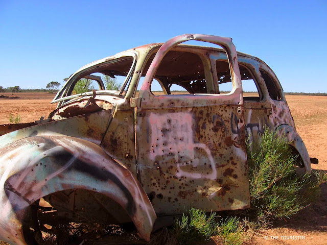 A broken and rusted beetle car left behind on the dusty red floor of the outback.