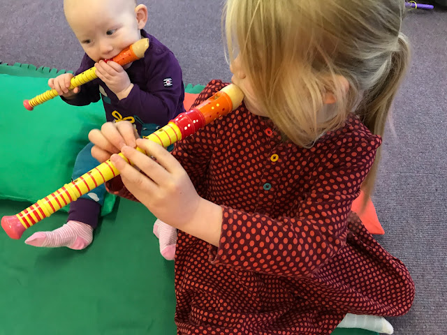 A baby and a 5 year old girl both attempting to play colourful recorders