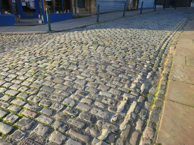 Cobbled road with white lines and stone pavement.