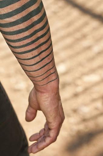 Preto braçadeiras de tornar-se gradualmente mais finos como eles perto do utente pulso neste tatuagem.
