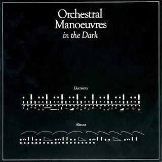 Portada del single Electricity OMD, 1979. Se trata de una especie de partitura con pequeños círculos, rayas y cuadrados blancos sobre fondo negro