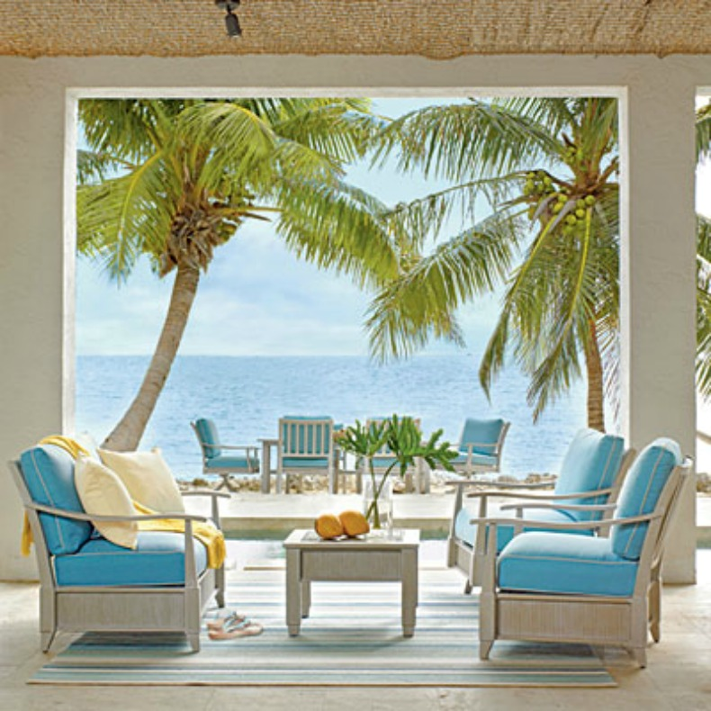 Beautiful coastal tropical lanai with whitewashed wood frame lounge chairs and aqua cushions