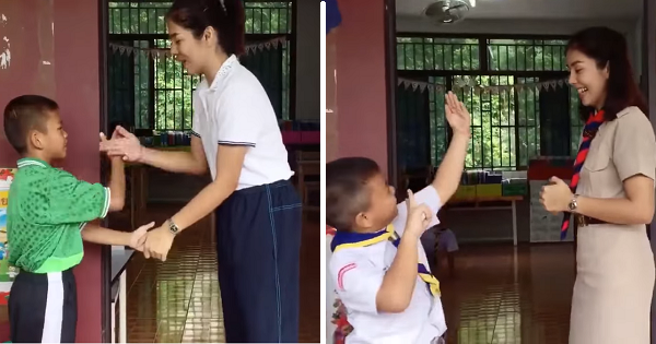 Teacher earns praise for greeting children with special handshake before class