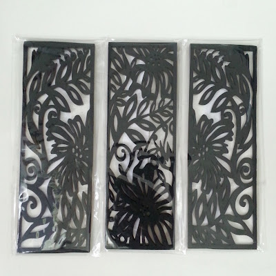 Three laser-cut wooden bookmark-sized black panels with Australian flora designs.