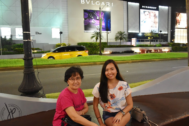 mother and daughter sitting at concrete bench along shopping street