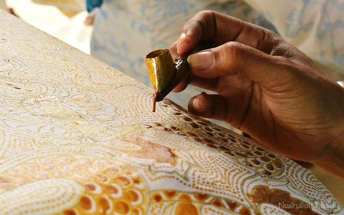 Jari-jari yang luwes memegang canting dan memberi warna motif pada kain