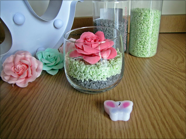 Dekoracyjne kamyczki z kwiatkiem  w szklanym naczyniu