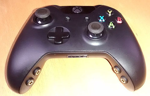Black joypad with four gold round sockets in the inner grips.