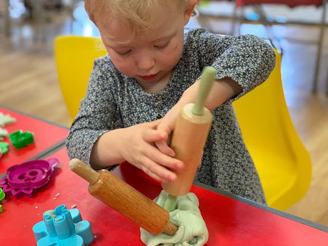 A toddler sticking rolling pins in playdough to pretend they are candles in a cake