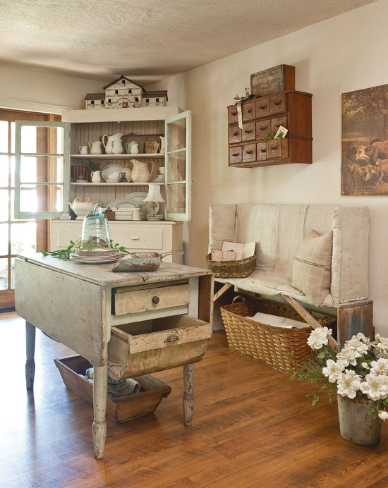 Woven and wooden baskets scattered around this country style kitchen look amazing with the rustic furniture