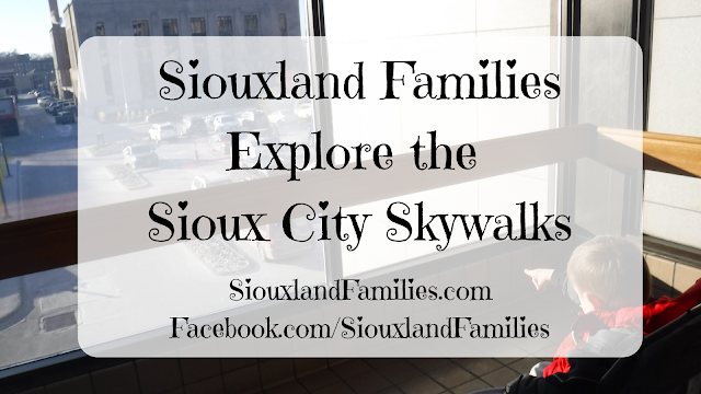 "in bachround, a boy in a stroller points out the window from the Sioux City Skwalk System in downtown Sioux City Iowa, in foregound the words ""Siouxland Families Explore the Sioux City Skywalks"""