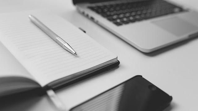 buku catatan, smartphone, dan laptop di atas meja putih