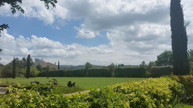 Weitläufige Rasenfläche mit blauen Himmel, Wolken, Bergen
