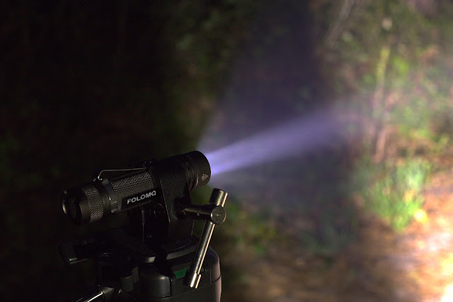 Wiązka światła latarki Folomov 18650s w mgiełce wilgotnego nocnego powietrza