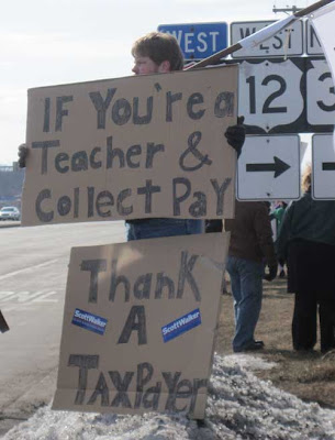 Counter demonstrator with two large signs reading If you're a teacher & collect pay thank a taxpayer, with two Scott Walker bumper stickers attached