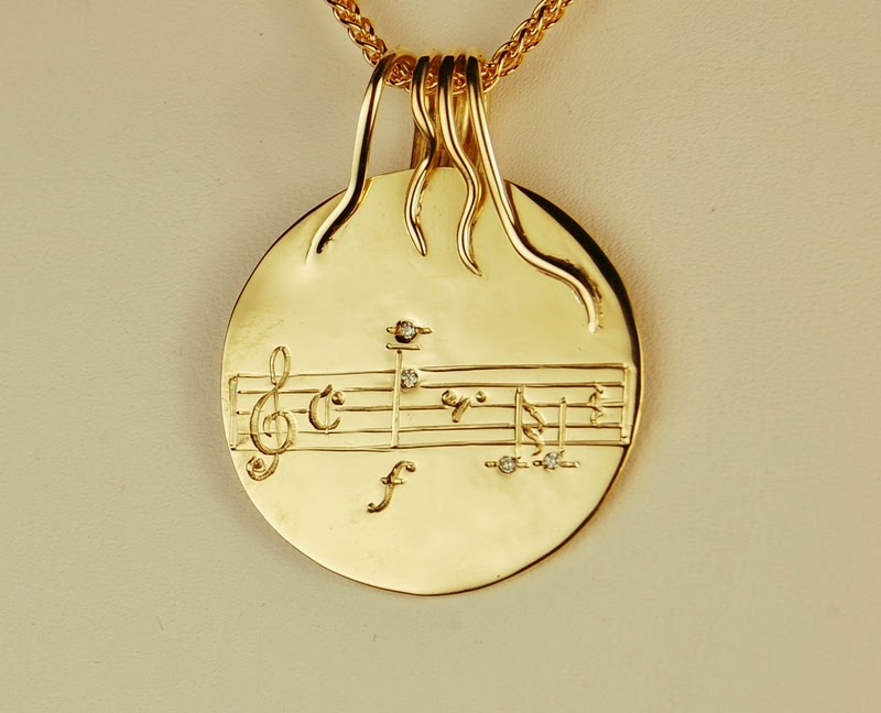 round disc pendant with engraved musical measure
