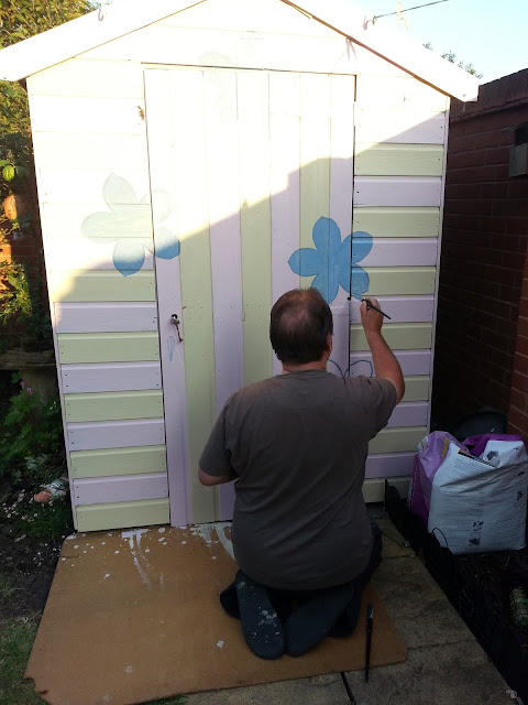 Man Painting Blue Flowers onto Striped Shed