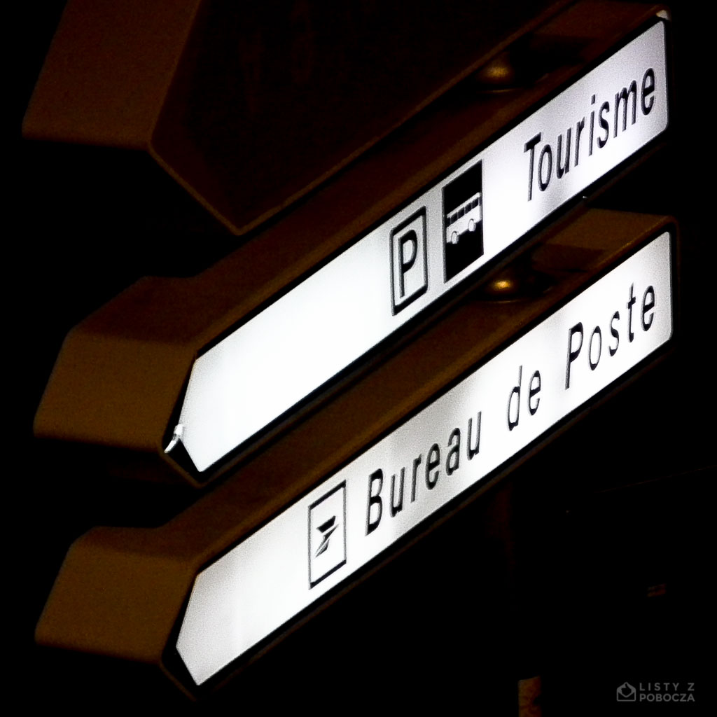 Lit street signs in France directing to Post Office