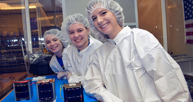 Mission manager Erin Puckette, center, prepares UVA's CubeSat for its upcoming launch. With her are team leaders Kim Wright of Old Dominion University, left, and Madison Brodnax of Virginia Tech. (Photo courtesy Virginia Space Grant Consortium)