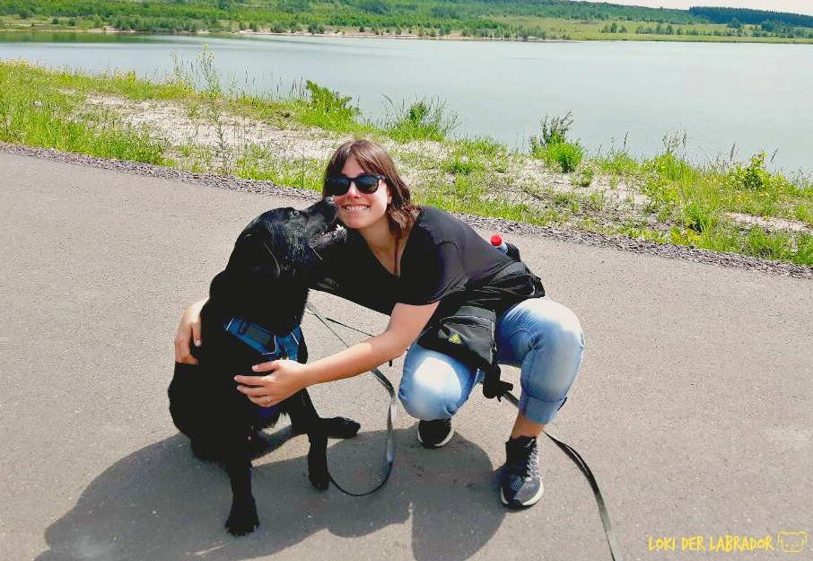 Schwarzer Labrador mit Frau am See