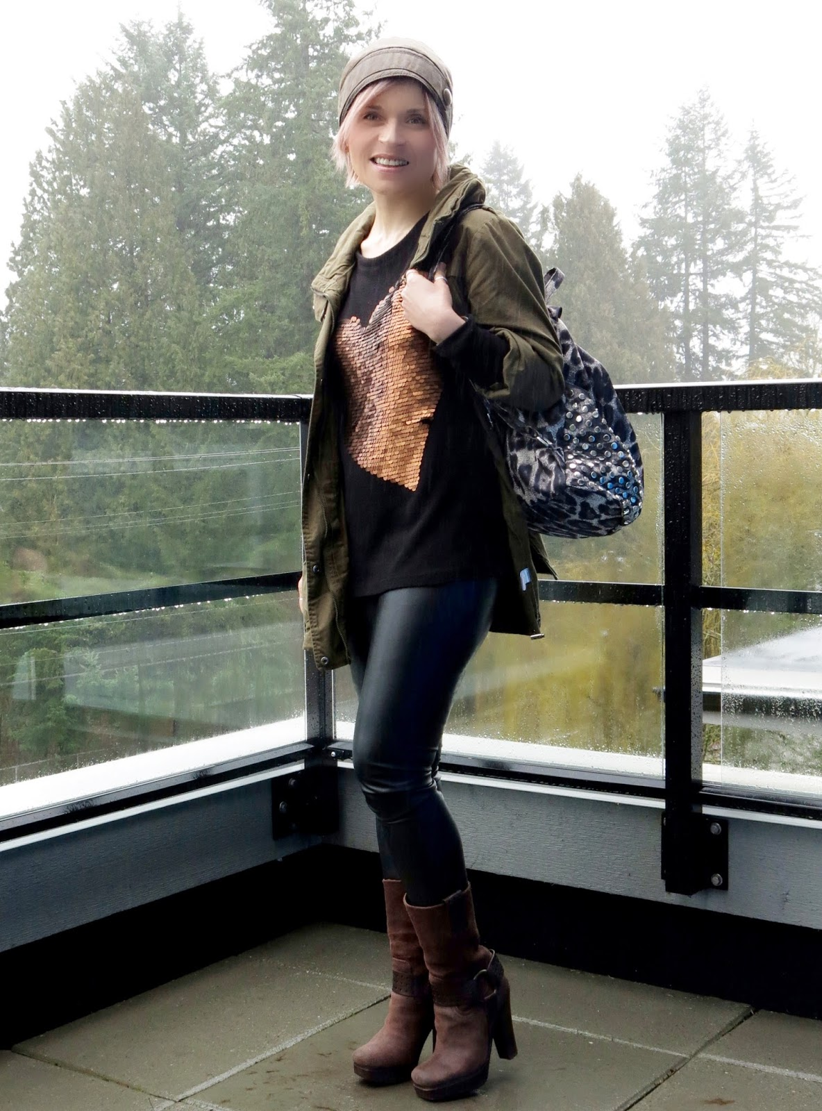 styling a sequinned sweater with an army parka, faux-leather leggings, leopard-print backpack, and leather beanie