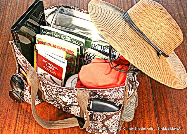 Organizer bag with watercolor art supplies for summer travel.