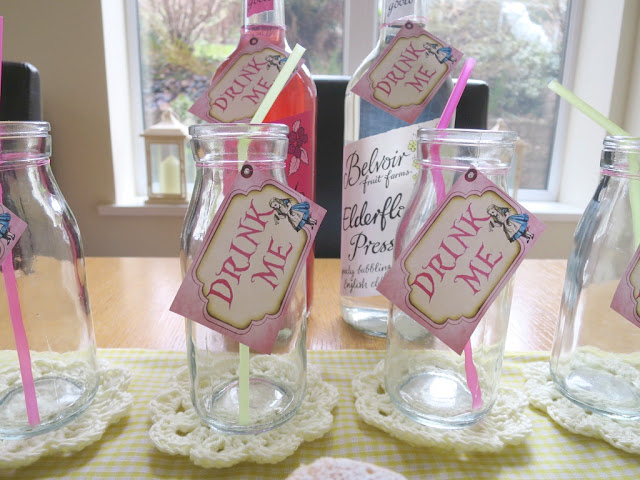 Home made birthday afternoon tea food and drink on Cath Kidston plates perfect for Spring flavoured lemonade in glass bottles with Alice in Wonderland Drink Me tags