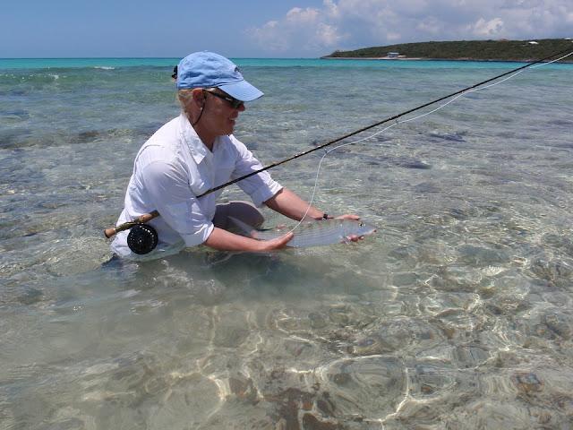 Una mujer pesca en una costa de Bahamas.