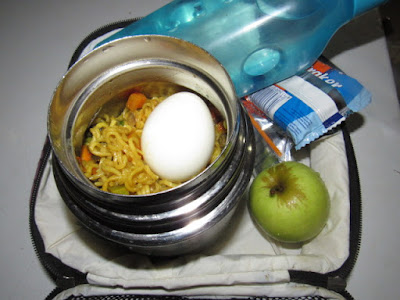 Nigerian school lunchbox meal of fried noodles with carrots, egg and served with apple