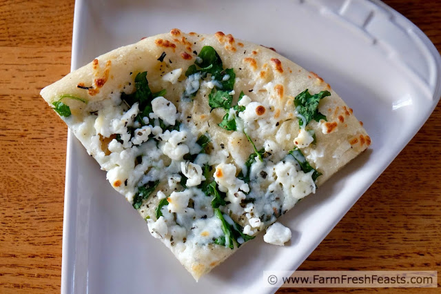 photo of a slice of white spinach pizza