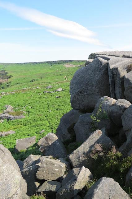 A view across moorland from the southern end of the escarpment to the northern end. Large rock formations fill the right hand side of the picture.