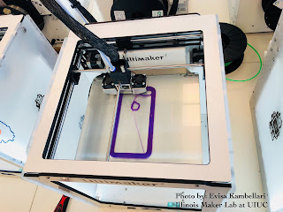 A photo of a 3D printer in action. It shows a purple rectangular object being printed inside of a glass box, on top of a glass plate.